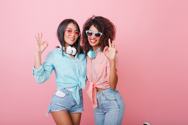 Schlanke amerikanische damen in der sommerkleidung, die mit glücklichem lächeln aufwirft. glamouröse kaukasische frau mit glänzender frisur, die freizeit mit afrikanischer freundin genießt.