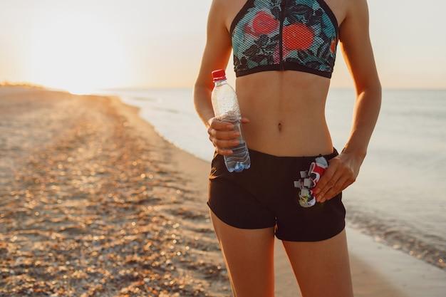 Schlanke, anmutige frau, die am strand steht und sich nach intensivem training entspannt. brünette frau hört musik, die nach dem training im freien pause macht.