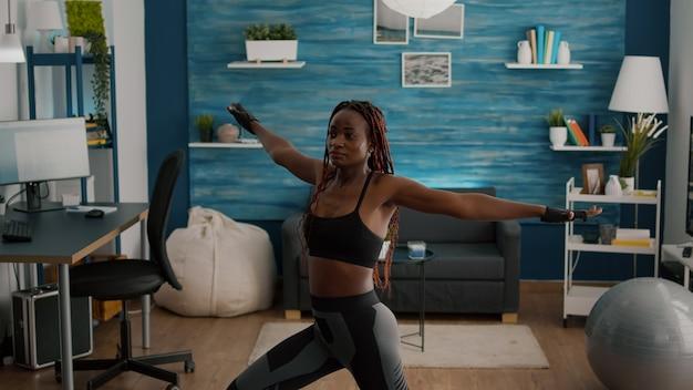 Schlanke, athetische junge frau mit sportbekleidung, die eine beinstandhaltung auf yoga-karte im wohnzimmer trägt