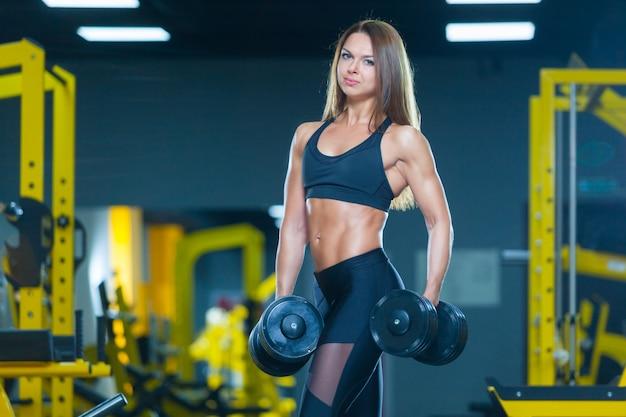 Schlanke athletische frau, die hanteln im fitnessstudio hält