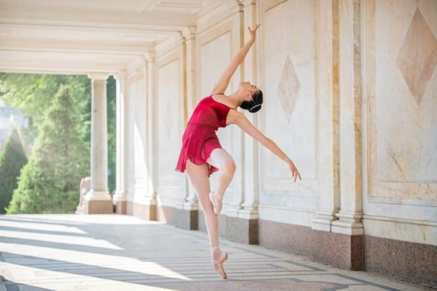 Schlanke ballerina in spitzenschuhen und silhouettenkostüm tanzen vor dem hintergrund der antiken architektur im park