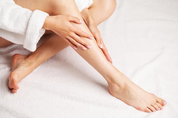 Schlanke beine der schönheitsfrau nach spa-therapie auf weißem hintergrund.
