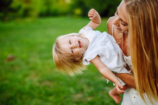 Schlanke blonde frau, die mit ihrer kleinen tochter im sommerpark spielt. mädchen tragen weiße kleider, familienblick.