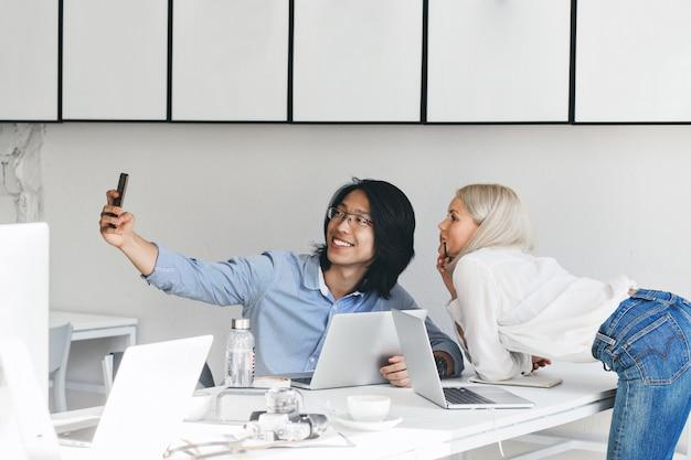 Schlanke blonde frau im weißen hemd und in den jeans, die neben tisch aufwerfen, während ihr asiatischer kollege selfie macht. innenporträt des chinesischen arbeiters in den gläsern, die spaß mit sekretärin haben.