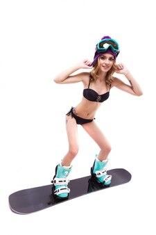 Schlanke blonde frau stehend auf snowboard