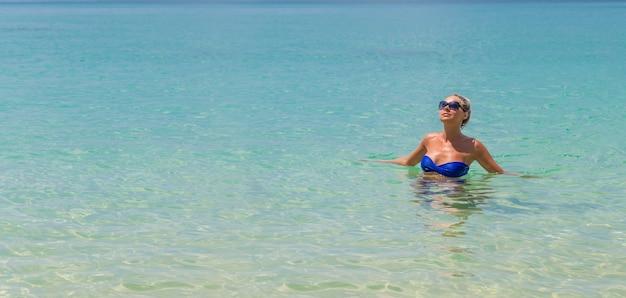 Schlanke blondine schwimmen am tropischen strand