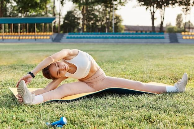 Schlanke brünette frau, die auf fitnesskaremat in nach oben angehobener schnur sitzt, yoga im freien macht, dame mit weißem oberteil und beige leggins, outdoor-aktivität.