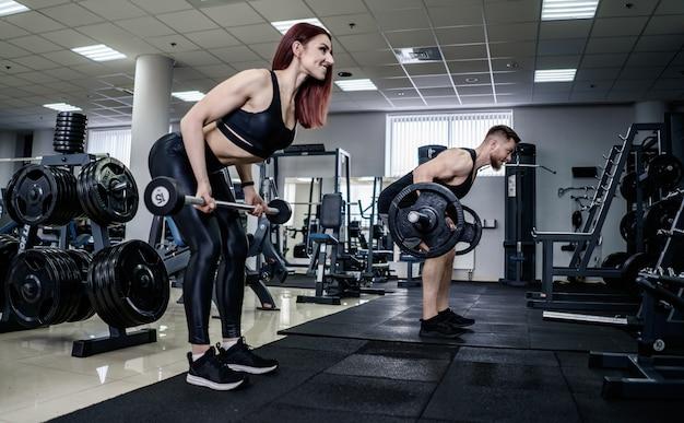 Schlanke brünette frau, die kniebeugen mit langhantel in der fitnesshalle tut