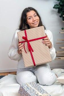 Schlanke brünette in einer weißen strickjacke mit einer weihnachtsgeschenkbox