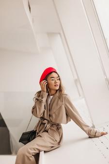 Schlanke dame in elegantem beigem trenchcoat und roter baskenmütze berührt ihr haar und sitzt am fenster an der weißen wand