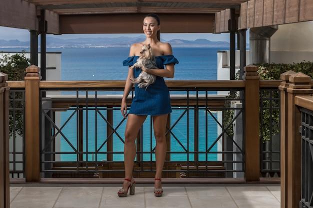 Schlanke dame mit kleinem hund auf der terrasse stehend
