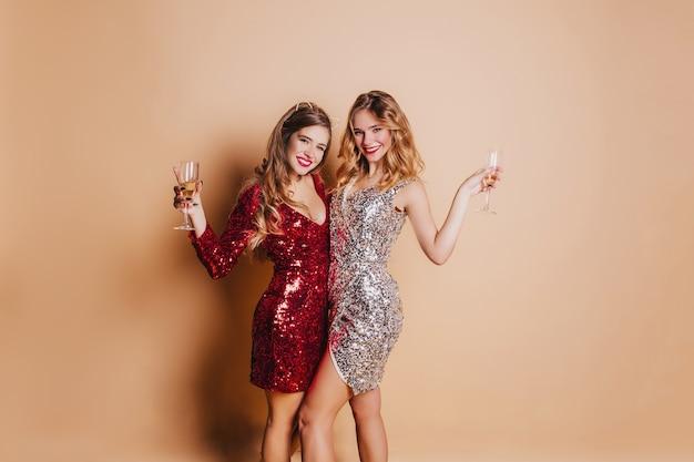 Schlanke damen in funkelnder kleidung posieren mit gläsern voller champagner und stehen auf einer hellen wand