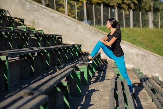 Schlanke fitnessfrau, die beine ausdehnt, bevor sie im stadion läuft. platz für text