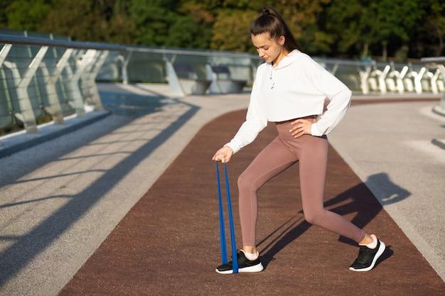 Schlanke fitnessfrau, die morgens mit gummiband an der brücke trainiert. leerer platz für text