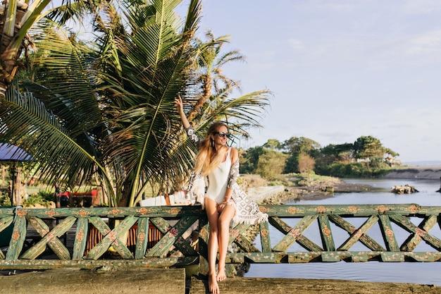 Schlanke frau, die an exotischem ort genießt. freudige gebräunte dame, die nahe palmen steht und lächelt.