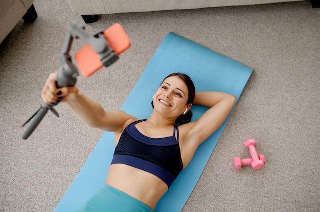 Schlanke frau, die auf matte liegt, online-fit-training mit telefon. weibliche person in sportbekleidung, internet-sporttraining, rauminnenraum