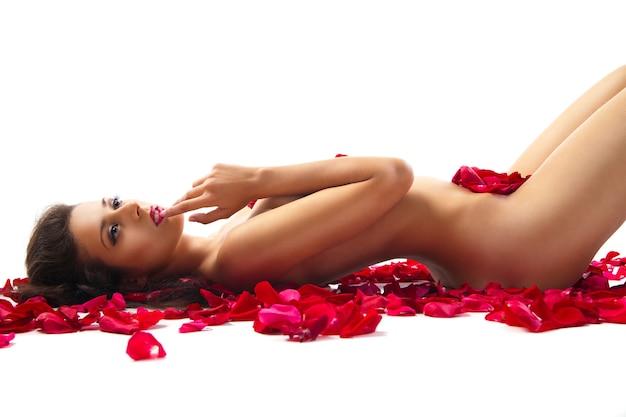 Schlanke frau, die auf roten rosenblättern über weiß liegt