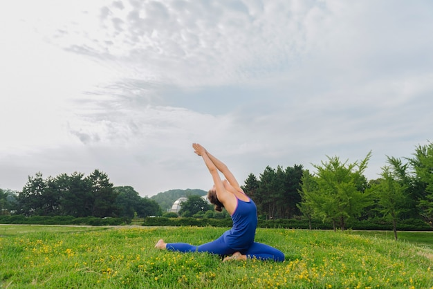 Schlanke frau, die dunkelblaue leggings trägt, die gute laune beim lieblingsmorgen-yoga haben