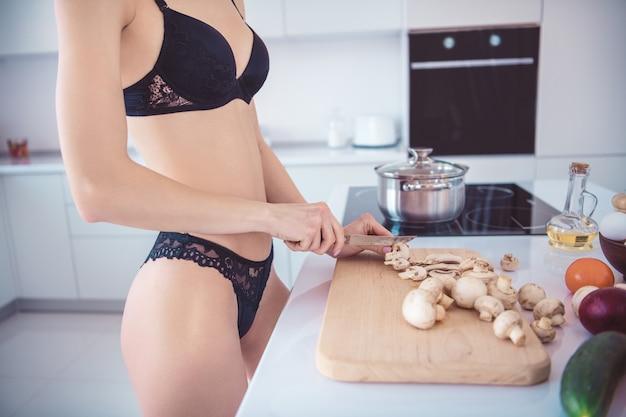 Schlanke frau, die in ihren dessous in der küche aufwirft