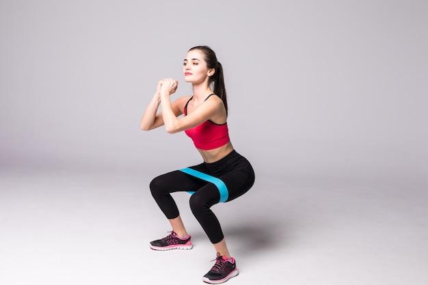 Schlanke frau, die kniebeugen mit elastischem fitness-schleifenband tut, das auf weißer wand lokalisiert wird
