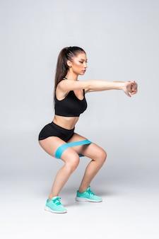 Schlanke frau, die kniebeugen mit fitnessschleifenband isoliert tut