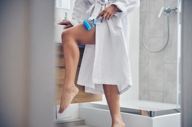 Schlanke frau, die sich während der lymphdrainage-massage an das waschbecken lehnt sink