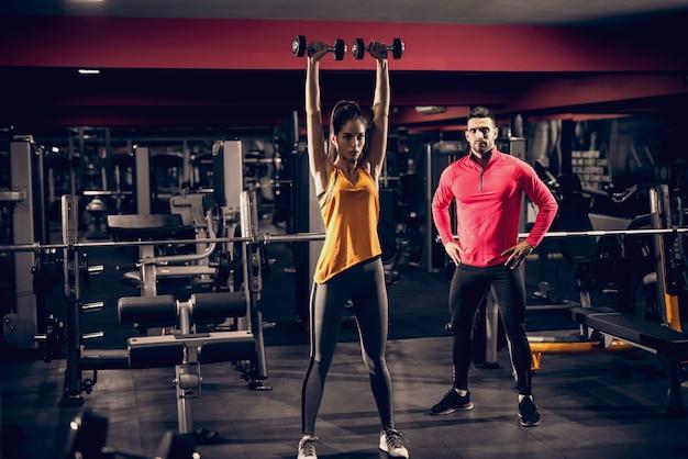 Schlanke frau, die übungen mit hanteln macht, während personal trainer sie beobachtet. im hintergrund trainingsgeräte.