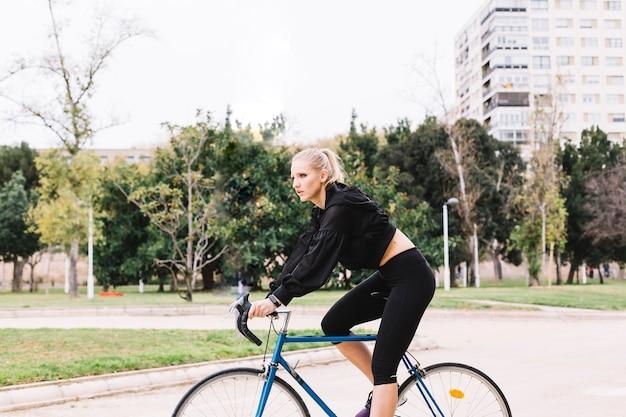 Schlanke frau e \ fahrrad im park fahren