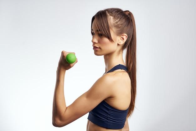 Schlanke frau fitness hanteln in den händen von starkem hellem hintergrund
