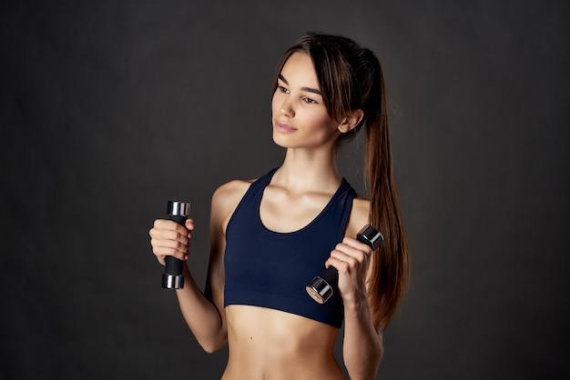 Schlanke frau fitness-übungshanteln in den händen von starkem dunklem hintergrund