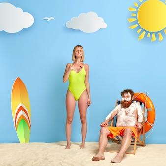 Schlanke frau im grünen bikini steht am sandstrand nahe rotschopf, der am strand mit sonnencreme aufwirft