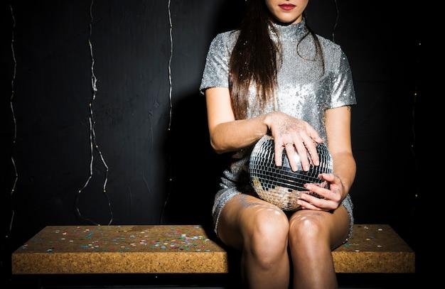 Schlanke frau im kleid mit discokugel