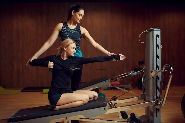 Schlanke frau in sportbekleidung auf pilates-training mit ausbilder auf trainingsgerät im fitnessstudio.