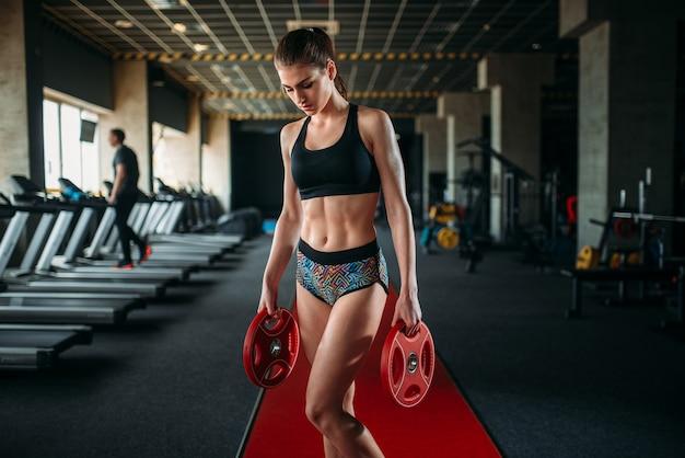 Schlanke frau in sportbekleidung hält gewicht in händen in sporthalle. training im fitnessclub