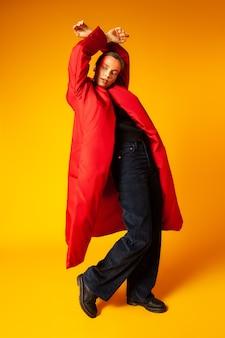 Schlanke frau in voller länge im trendigen übergroßen mantel, der weg schaut und gegen gelben hintergrund tanzt