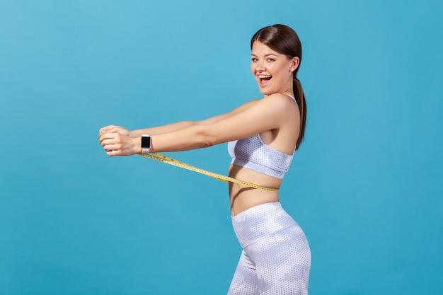 Schlanke frau in weißer sportkleidung, die sich am taillenbandmaß festhält und zufrieden in die kamera schaut Premium Fotos