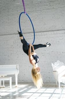 Schlanke frau ist in der luftgymnastik mit einem kreis beschäftigt