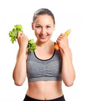 Schlanke frau mit einer schönen figur hält gemüse in den händen - karotten und salat