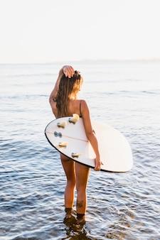 Schlanke frau mit surfbrett im meer