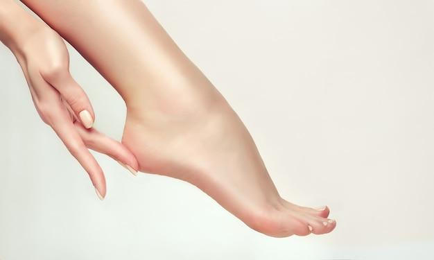 Schlanke frauenfinger berühren die gepflegte ferse des grace foot spa epilation und fußpflege