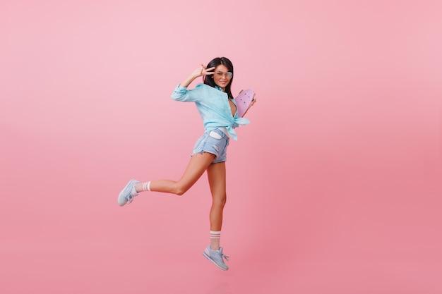 Schlanke gebräunte asiatische dame mit laufendem longboard. raffiniertes sportliches hipster-mädchen, das mit skateboard genießt.