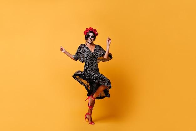 Schlanke gebräunte mexikanerin mit blumenkrone springt und tanzt mit orangefarbenen wänden