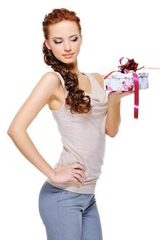 Schlanke junge frau der schönheit, die in der hand kleine weiße geschenkbox mit einem roten band hält