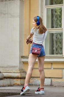 Schlanke junge frau, die tanzt, während sie musik durch kopfhörer im freien hört.