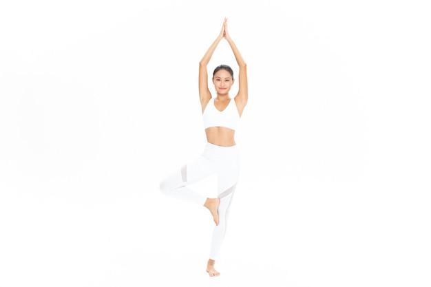 Schlanke junge frau praktiziert yoga isoliert