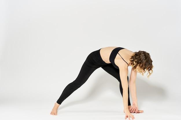 Schlanke junge frau praktiziert yoga und übungen zu hause