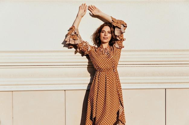 Schlanke kaukasische frau mit tätowierung, die im eleganten weinlesekleid aufwirft. foto der interessierten dame mit gewelltem haar trägt braunes kleid.