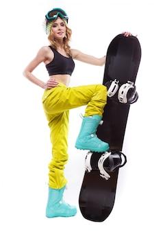 Schlanke mädchen steht mit snowboard ein bein auf
