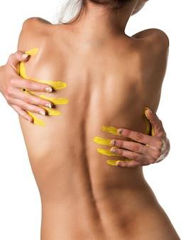 Schlanke nackte junge frau mit tätowierung, die rückwärts mit gelben fingerabdrücken auf ihrem rücken steht