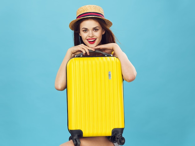 Schlanke schöne frau bereitet sich auf urlaub vor und sammelt einen koffer, einen gelben koffer, einen badeanzughut, ein bild für den urlaub